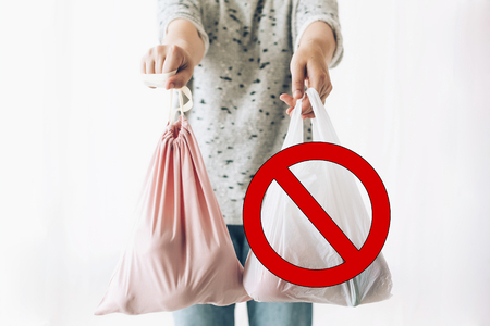 Ban single use plastic, stop sign. Zero Waste shopping concept. Woman holding in one hand groceries in reusable eco bag and in other vegetables in plastic polyethylene bag.
