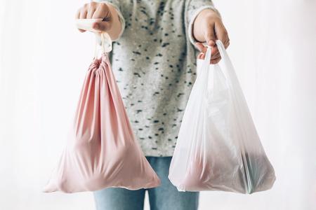 Kobieta trzymająca w jednej ręce zakupy w eko torebce wielokrotnego użytku, a w drugiej warzywa w plastikowej torbie polietylenowej. Wybierz artykuły bez plastiku. Zakaz plastiku jednorazowego użytku. Koncepcja zakupów zero odpadów.