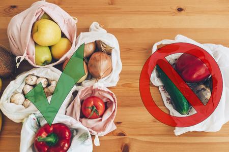 Divieto di plastica monouso. Concetto di acquisto dei rifiuti zero. Generi alimentari freschi in sacchetti ecologici riutilizzabili e verdure in sacchetto di plastica in polietilene su tavola di legno. Scegli articoli senza plastica.
