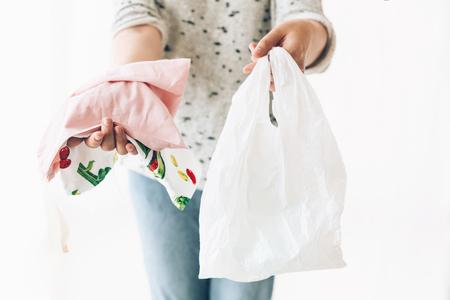 Divieto di plastica monouso. Concetto di acquisto dei rifiuti zero. Donna che tiene in una mano la spesa in un sacchetto ecologico riutilizzabile e in altre verdure in un sacchetto di plastica in polietilene. Scegli articoli senza plastica.