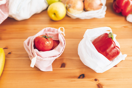 Zero Waste shopping concept. Fresh groceries in reusable eco bags and vegetables in plastic polyethylene bag on wooden table. Choose plastic free items. Ban single use plastic