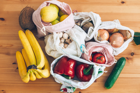 Fresh groceries in eco cotton bags on wooden table, flat lay. Zero Waste shopping concept. Vegetables from market in reusable bags. Ban single use plastic. Sustainable lifestyle