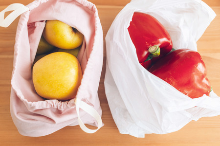 Fresh groceries in reusable eco bags and vegetables in plastic polyethylene bag on wooden table. Ban single use plastic. Choose plastic free items. Reuse, reduce. Zero Waste shopping concept Foto de archivo