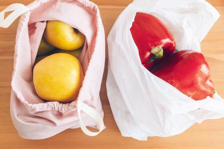 Frische Lebensmittel in wiederverwendbaren Öko-Taschen und Gemüse in Plastiktüten aus Polyethylen auf Holztisch. Einwegplastik verbieten. Wählen Sie plastikfreie Artikel. Wiederverwenden, reduzieren. Zero Waste Einkaufskonzept Standard-Bild