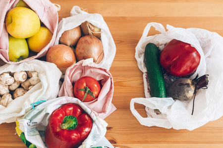 Fresh groceries in reusable eco bags and vegetables in plastic polyethylene bag on wooden table. Ban single use plastic. Choose plastic free items. Reuse, reduce. Zero Waste shopping concept Stock Photo