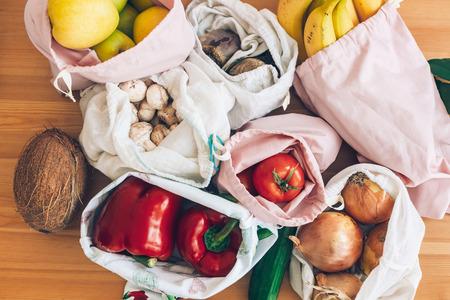 Generi alimentari freschi in sacchetti di cotone ecologico su tavola di legno, distesi piatti. Concetto di acquisto dei rifiuti zero. Verdure dal mercato in sacchetti riutilizzabili. Divieto di plastica monouso. Stile di vita sostenibile