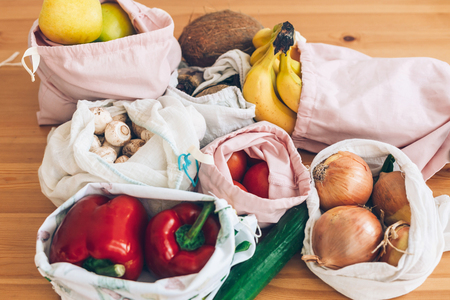 Zero Waste shopping concept. Fresh vegetables pepper, beets, tomatoes, cucumber, bananas, onions, coconut, mushrooms, apples in reusable eco bags on wooden table. Ban single use plastic