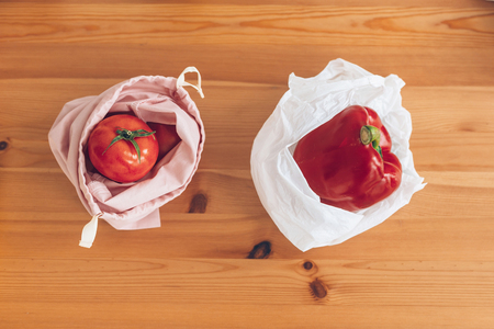 Zero Waste shopping, flat lay. Fresh groceries in reusable eco bags and vegetables in plastic polyethylene bag on wooden table. Ban single use plastic. Choose plastic free items. Reuse, reduce. Stock Photo