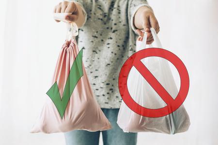 Einwegplastik verbieten, Stoppschild. Wählen Sie plastikfrei. Zero-Waste-Shopping-Konzept. Frau, die in einer Hand Lebensmittel in einer wiederverwendbaren Öko-Tasche und in anderem Gemüse in einer Plastiktüte aus Polyethylen hält Standard-Bild