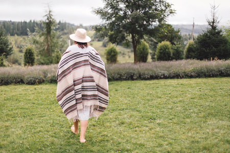 Stylish hipster girl in poncho, linen dress and hat walking at lavender field and relaxing in the morning. Bohemian woman enjoying vacation in mountains. Atmospheric rustic moment. Copy space