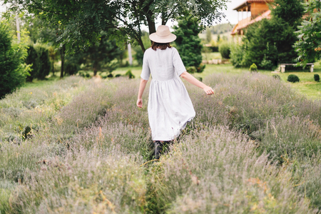 Stylish hipster girl in linen dress and hat walking in lavender field and relaxing. Happy bohemian woman enjoying lavender aroma in summer mountains. Atmospheric calm rural moment