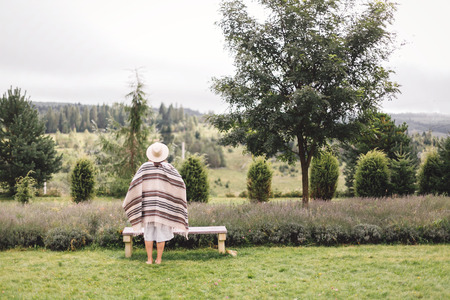 Stylish hipster girl in poncho, linen dress and hat posing at lavender field and relaxing in the morning. Bohemian woman enjoying vacation in mountains. Atmospheric rustic moment. Copy space