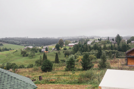 Beautiful hill with houses and trees  in foggy morning mountains. Summer vacation in countryside.  Atmospheric rustic moment. Copy space