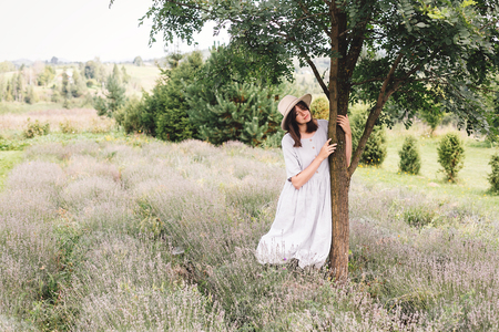 Stylish hipster girl in linen dress and hat relaxing in lavender field near tree. Happy bohemian woman enjoying summer vacation in mountains. Atmospheric calm rural moment. Space for text