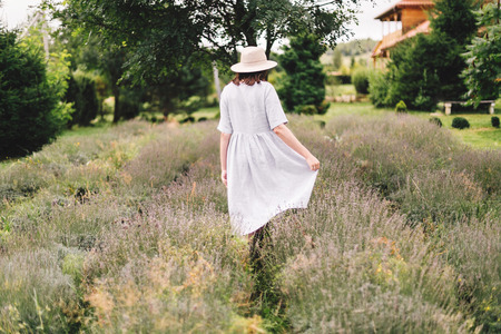 Stylish hipster girl in linen dress and hat walking in lavender field and relaxing. Happy bohemian woman enjoying lavender aroma. Back view. Atmospheric calm rural moment. Space for text