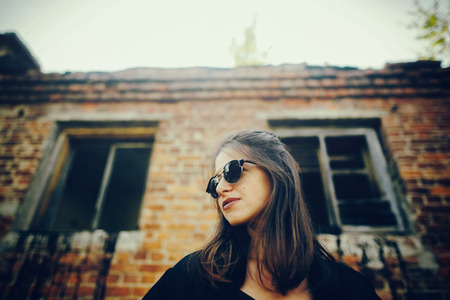 Stylish hipster girl posing in street, atmospheric moment. Fashionable cool woman in black sunglasses standing at old brick building. Selective focus. Space text. Retro effect Stock Photo