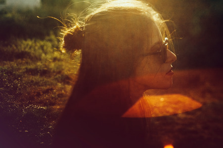 Stylish hipster girl posing in sunny park with amazing sun beams, atmospheric moment. Fashionable woman portrait in sunglasses in evening. Selective focus. Retro effect. Creative image