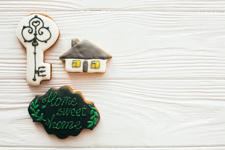 Moving in new house, Welcome home set. Key, house, welcome sign cookies on white wood, flat lay with space for text. Dream home concept. Home Sweet Home.