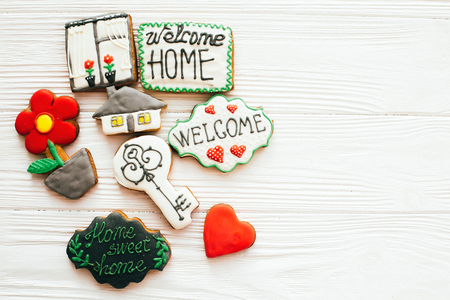 Delicious key, house, plant,window,heart and welcome sign cookies on white wood, flat lay with space for text. Dream home concept. Sweet Home. Moving in new house, Welcome home set.