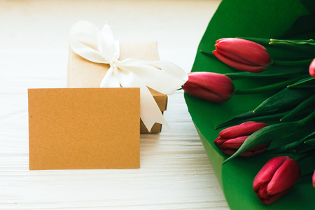 Happy mothers day. Beautiful red tulips bouquet in green paper,gift box and craft card with space for text on white wooden background. Pink tulips on white wood. Greeting card template