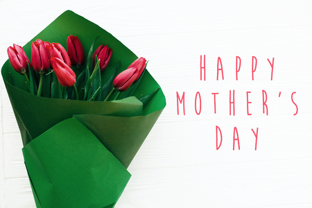 Happy Mother's Day text and beautiful red tulips on white wooden background flat lay. Happy mother day greeting card with spring flowers. Stylish simple holiday card