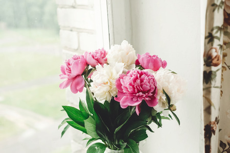 Beautiful pink and white peonies bouquet at rustic old wooden window. Floral decor and arrangement. Gathering flowers. Rural still life, countryside. Copy space 스톡 콘텐츠 - 122224215
