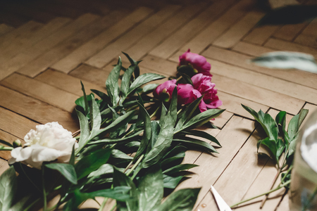 Beautiful pink and white peonies on rustic wooden floor with old glass jar and scissors. Copy space. Floral decor and arrangement. Gathering flowers. Rural still life, countryside flowers Фото со стока - 122224218