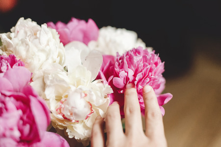 Hand holding beautiful pink and white peonies petals bouquet in glass jar on rustic wooden floor. Floral decor and arrangement. Gathering flowers. Rural still life, countryside Banque d'images - 122224298