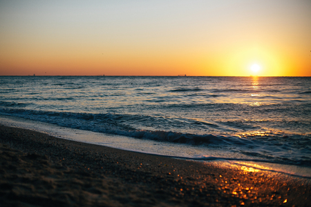 Beautiful sea waves foam closeup and red sky with sun in sunrise light on tropical island. Waves in ocean at sunset. Tranquil calm moment. Summer vacation. Copy space Reklamní fotografie