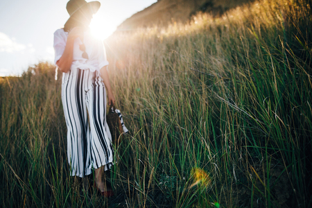 Grass in sunny evening light at sandy cliff near sea and blurred boho girl in hat posing in sun. Happy young hipster woman relaxing on tropical island beach. Summer vacation. Space for text