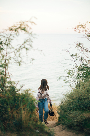 Stylish hipster girl walking on beach at sea. Happy fashionable boho woman relaxing at sandy cliff on tropical island and looking at water. Travel and summer vacation. Space for text