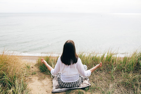 Yoga day. Stylish hipster girl sitting on beach in yoga pose and relaxing. Happy boho woman practicing yoga and meditation at sea on tropical island. Mindful concept. Space for text Reklamní fotografie
