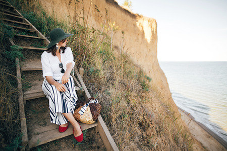 Stylish boho girl in hat sitting on wooden stairs in sunny light at sandy cliff near sea. Happy young fashionable woman relaxing on tropical island beach. Summer vacation. Space for text