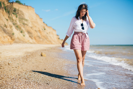Stylish hipster girl relaxing on beach and having fun.  Happy young boho woman walking and smiling in sea waves in sunny warm day on tropical island. Summer vacation. Space for text