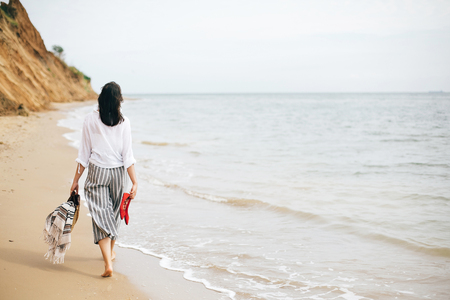 Stylish hipster girl walking barefoot on beach, holding bag and shoes in hand. Summer vacation. Space for text. Calm moment. Happy boho woman relaxing at sea, enjoying walk on tropical island