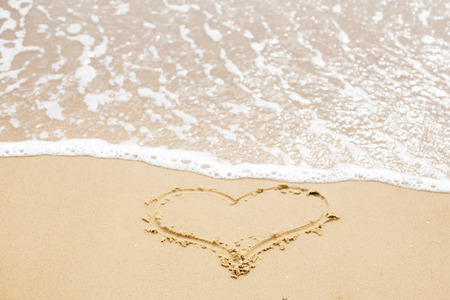 Heart sign on beach. Heart symbol on sandy beach and sea waves with foam. Love and hello summer concept. Vacation, relax and travel. Copy space. Valentine day gift Stock Photo
