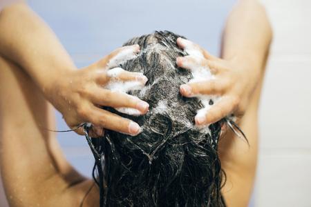Jonge gelukkige vrouw die haar haar wast met shampoo, handen met schuimclose-up. Achterkant van mooie brunette meisje douche nemen en genieten van ontspannen tijd. Lichaams- en haarhygiëne, lifestyle concept