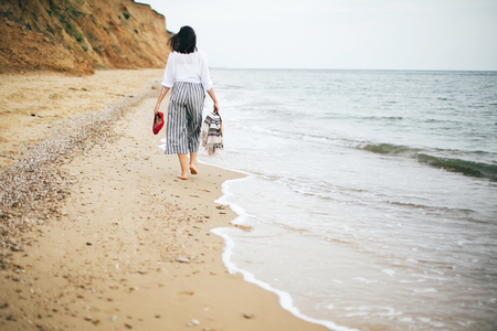 Stylish hipster girl walking barefoot on beach, holding bag and shoes in hand. Happy boho woman relaxing at sea, enjoying walk on tropical island. Summer vacation. Space for text.