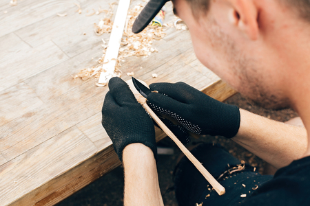 Wooden workshop. Hands carving spoon from wood, working with chisel close up. Process of making wooden spoon, chisel and shavings on dirty table. Handmade festival in summer park