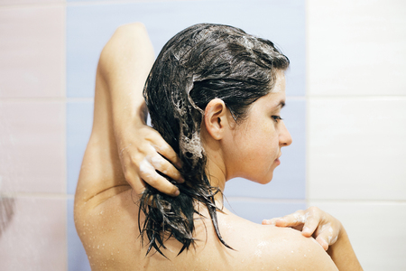 Young happy woman washing her hair with shampoo, foaming with hands. Beautiful  brunette girl taking shower and enjoying relax time. Body, hair and skin hygiene, lifestyle concept.