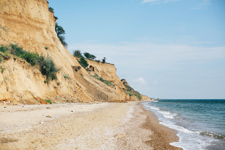 Beautiful sandy cliff with grass and sea waves on beach with on tropical island. Big rock and waves in ocean bay or lagoon. Tranquil calm moment. Summer vacation. Copy space