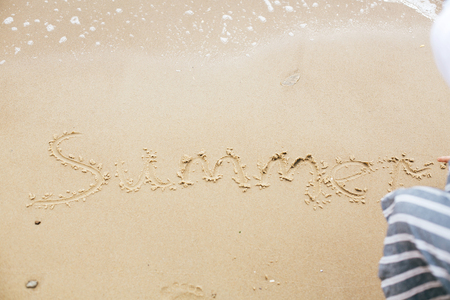Summer sign on beach. Girl writing summer text on sandy beach at sea. Hello summer concept. Vacation, relax and travel. Stock Photo