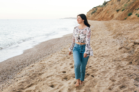 Stylish hipster girl walking on beach at sea and relaxing. Happy boho woman in denim jeans and floral blouse relaxing at sandy cliff on tropical island. Travel and summer vacation concept Stock Photo