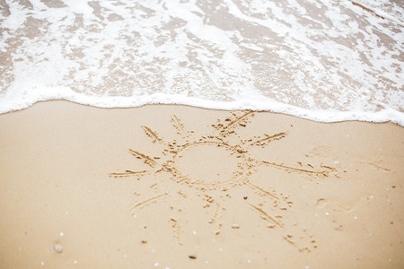 Sun sign on beach. Summer text, sun symbol on sandy beach with footprints and sea waves foam. Hello summer concept. Vacation, relax and travel. Copy space