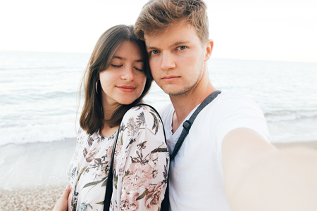 Stylish hipster couple taking selfie on beach at evening sea. Summer vacation. Portrait of happy young family on honeymoon on tropical island making selfie. Space for text Stock Photo