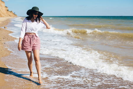 Summer vacation. Happy young boho woman walking and having fun in sea waves in sunny warm day on tropical island. Space for text. Stylish hipster girl in hat relaxing on beach and smiling Banque d'images