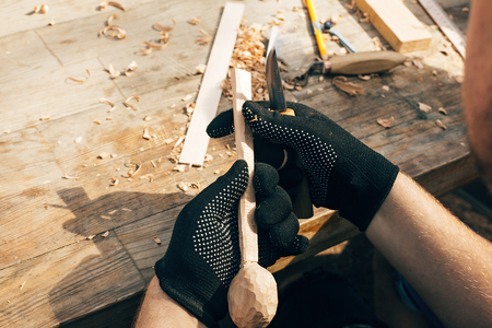 Wooden workshop. Hands carving spoon from wood, working with chisel close up. Process of making wooden spoon, chisel, pencil, compass, ruler on dirty table with shavings