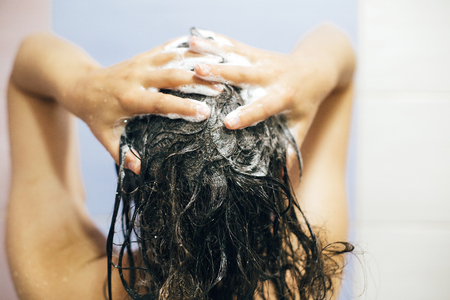 Young happy woman washing her hair with shampoo, hands with foam closeup. Back of beautiful brunette girl taking shower and enjoying relax time. Body and hair hygiene, lifestyle concept