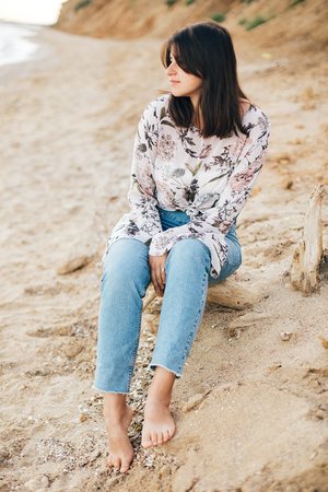 Stylish hipster girl sitting on beach at sea. Happy fashionable boho woman in denim jeans and floral blouse relaxing at sandy cliff on tropical island. Travel and summer vacation Stock Photo