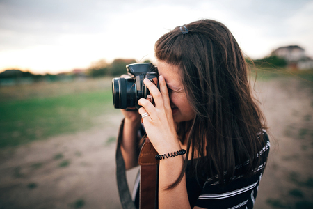 Stylish hipster girl taking photos on beach at sunset. Summer vacation. Portrait of  happy boho woman holding photo camera and making photos in evening time at  sea cliff Foto de archivo - 123769104